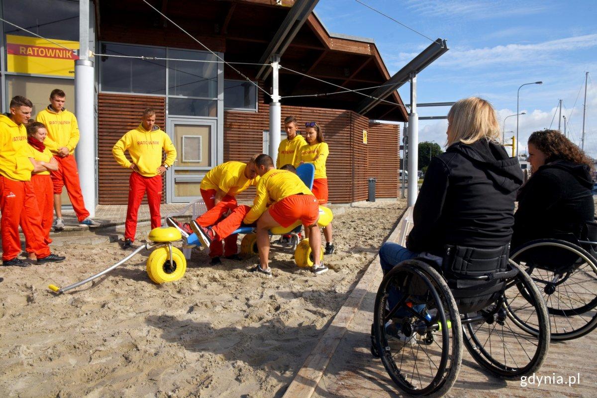 W Śródmieściu osoby z niepełnosprawnością mogą skorzystać z wózka kąpielowego, który umożliwia transport po piasku oraz bezpośredni kontakt z morską wodą. / Zdjęcie ze szkolenia ratowników w 2019 roku, fot. Jan Ziarnicki