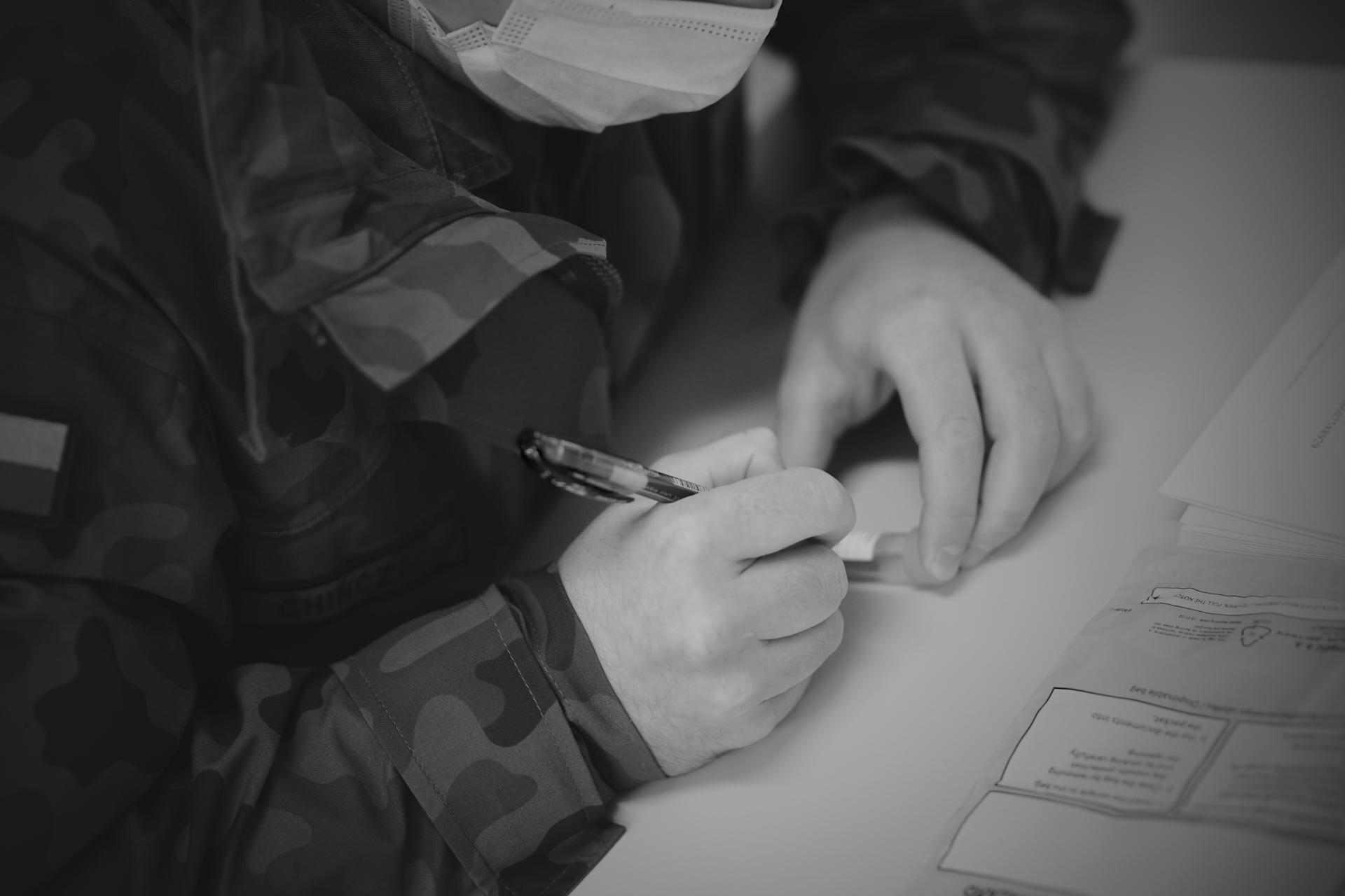 Jeden z żołnierzy w maseczce i z długopisem w ręku podpisuje próbkę. Przed nim na stole leży przezroczysty woreczek ochronny // fot. st. chor. szt. mar. Piotr Leoniak