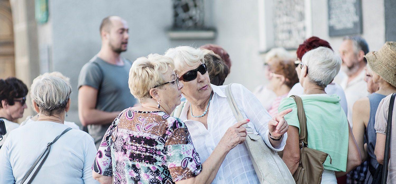 Dwie kobiety na tle tłumu ludzi. Jedna z nich posiada okulary przeciwsłoneczne. Obracają się w prawą stronę, wskazując przy tym dłonią..