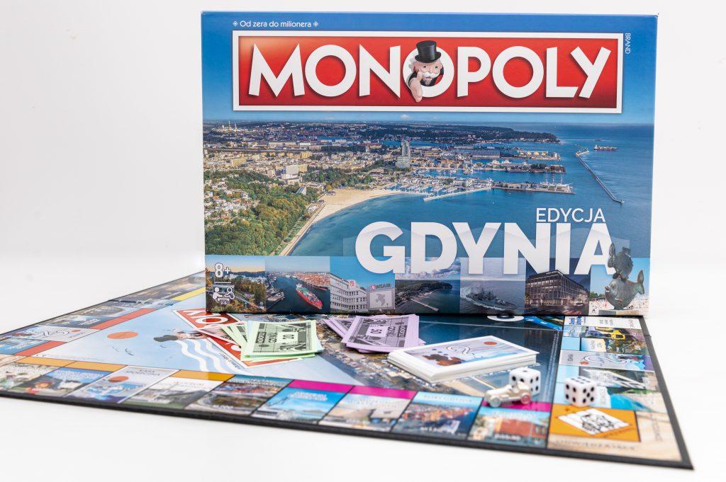 Gra planszowa Monopoly Edycja Gdynia. Na zdjęciu widoczne jest opakowanie gry oraz rozłożona plansza z kolorowymi banknotami. // fot. gck.gdynia.pl/sklep