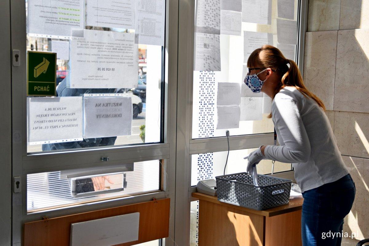 Pracownica Urzędu Miasta Gdyni stoi obok wrzutni na dokumenty przy  wejściu do ratusza. Na rękach ma białe rękawiczki, a na twarzy maseczkę ochronną // fot. Paweł Kukla