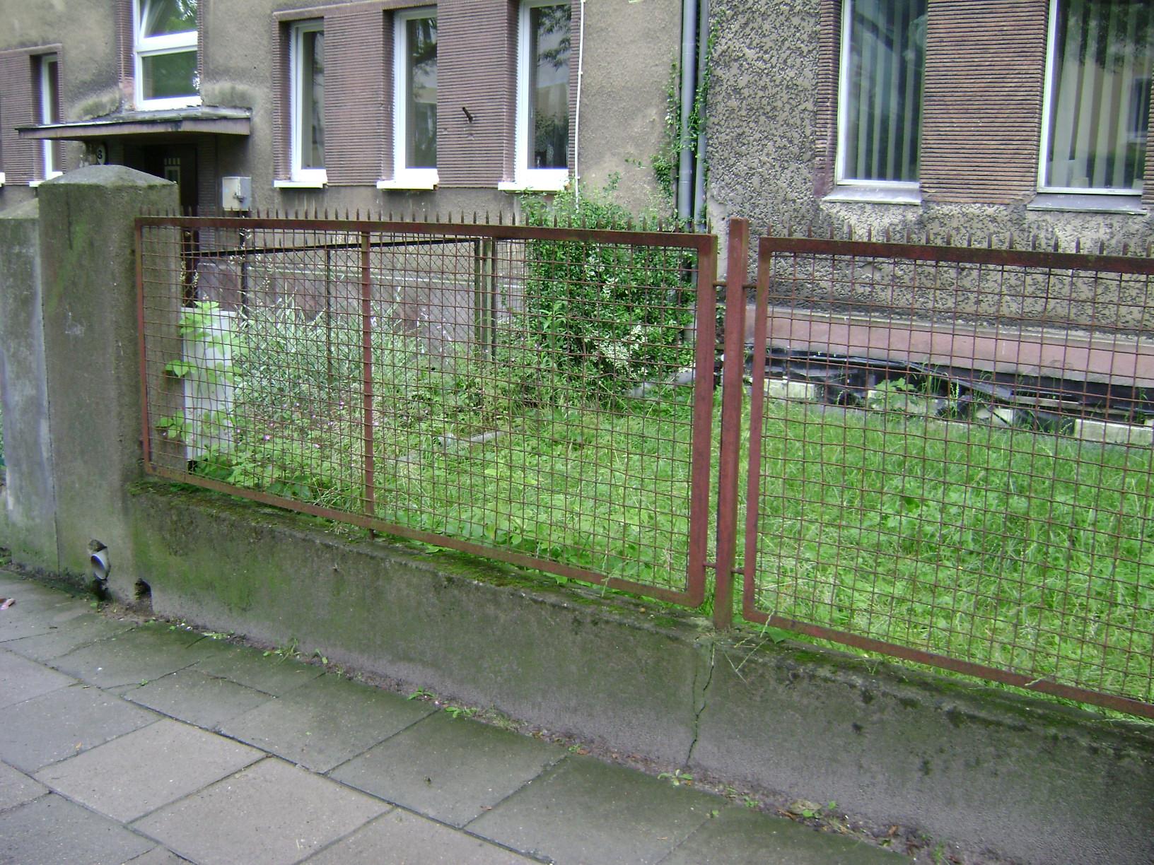Ogrodzenie z metalowej siatki w ramach mocowanych do murowanych słupków, charakterystyczne dla lat 30. XX w.