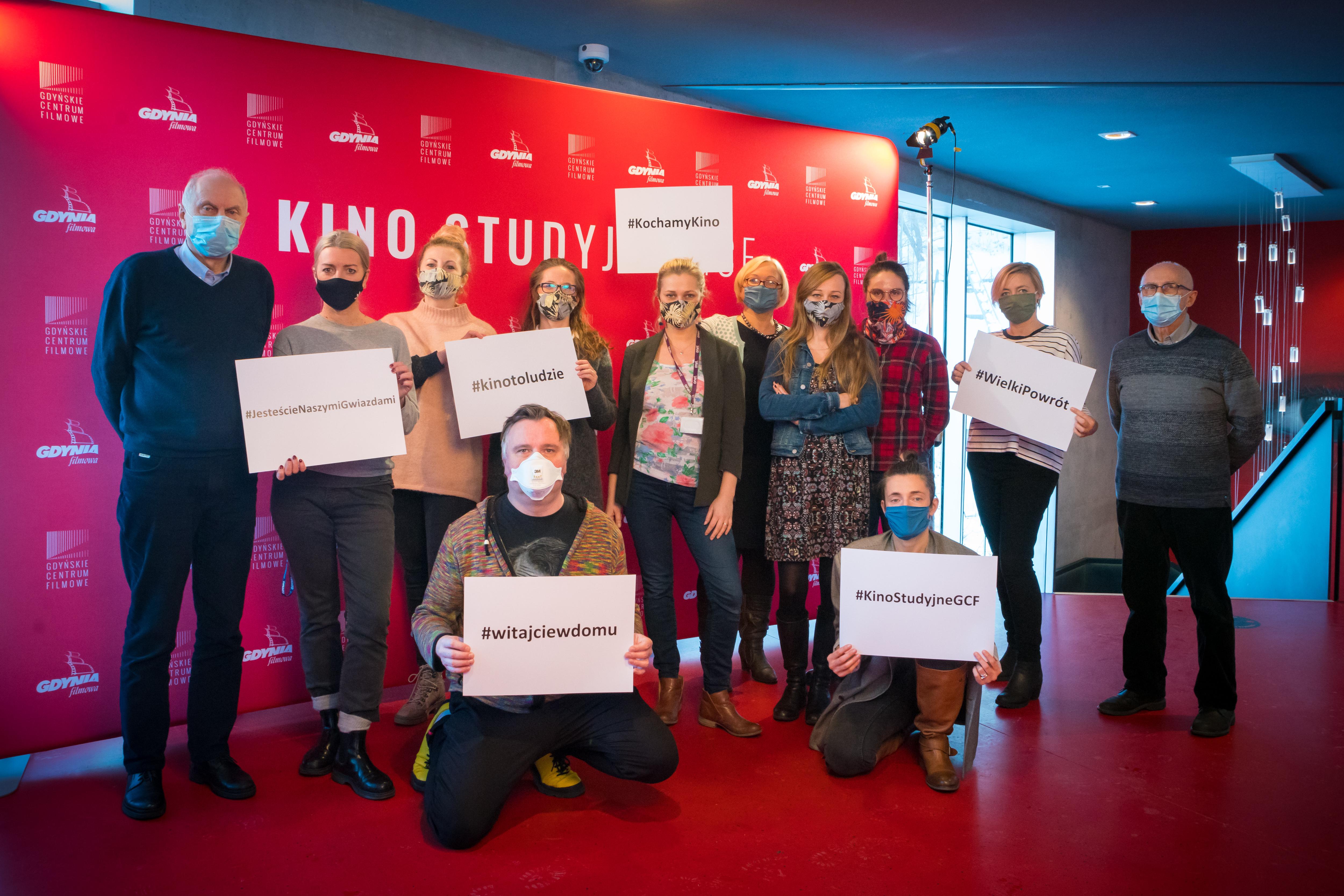 """Grupa 12. osób zebrała się przed ścianką Gdyńskiego Centrum Filmowego. Osoby na zdjęciu mają założone maseczki, a niektóre osoby trzymają kartki z napisami """"#witajciewdomu"""", """"#kinotoludzie"""", """"#kochamykino"""". // fot. Anna Rezulak / KFP"""