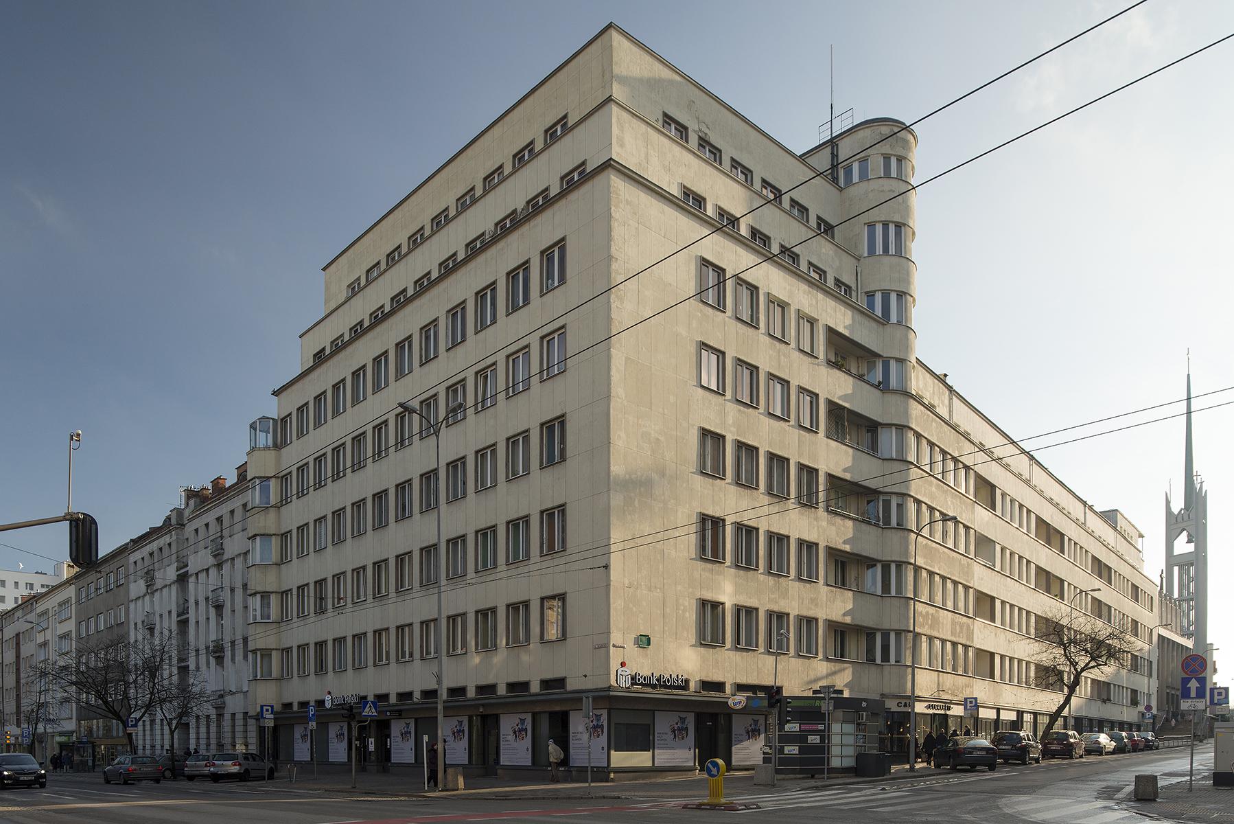 Na zdjęciu budynek przy ul. 3 Maja 27-31. Elewacje powyżej parteru wykończone są okładziną z płyt kamiennych z wapienia pińczowskiego