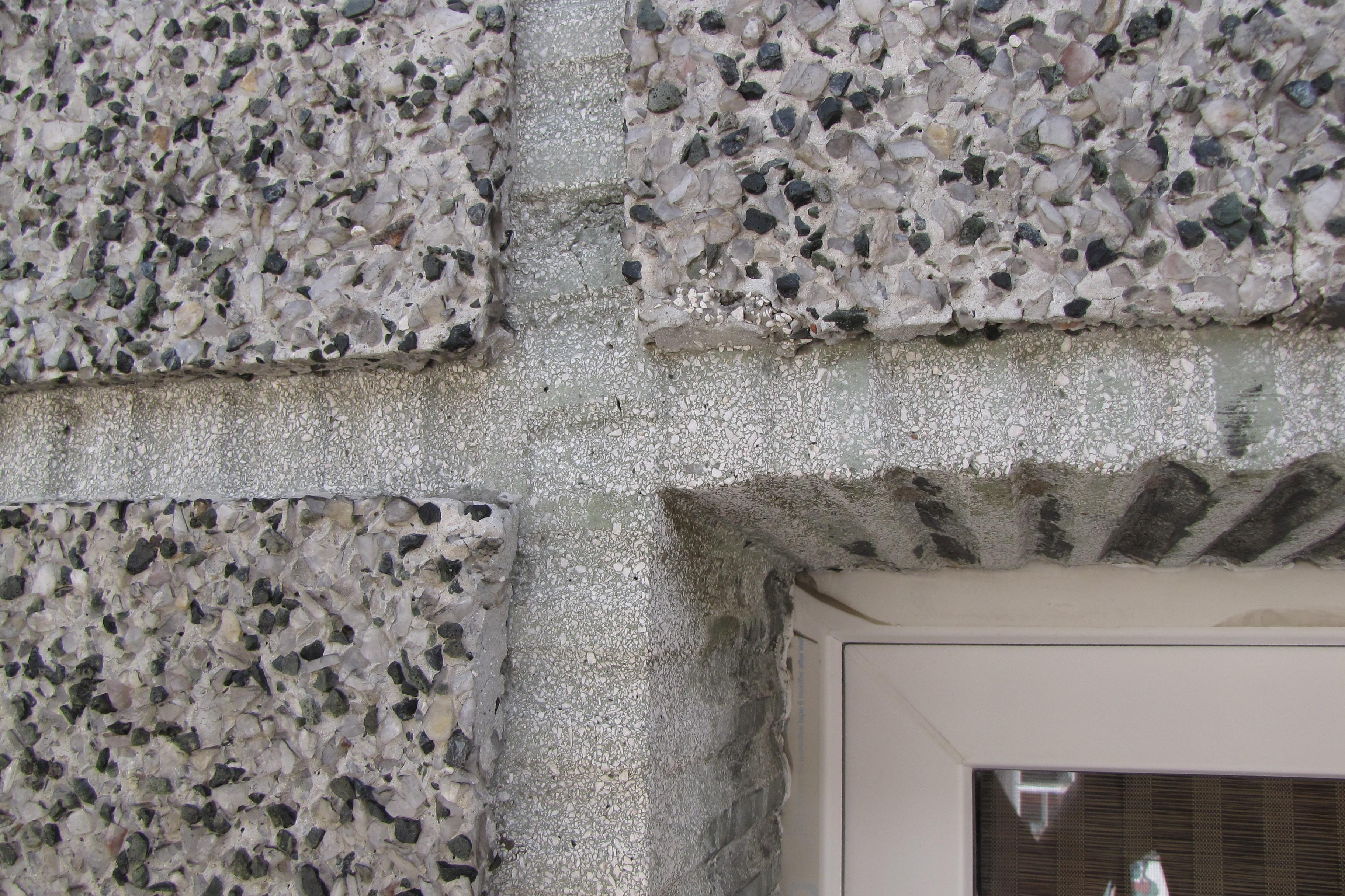 Szczegół tynku z elewacji kamienicy ul. Świętojańskiej 105, z widocznymi grubymi ziarnami, które uwydatniono wypłukując zaprawę z powierzchni