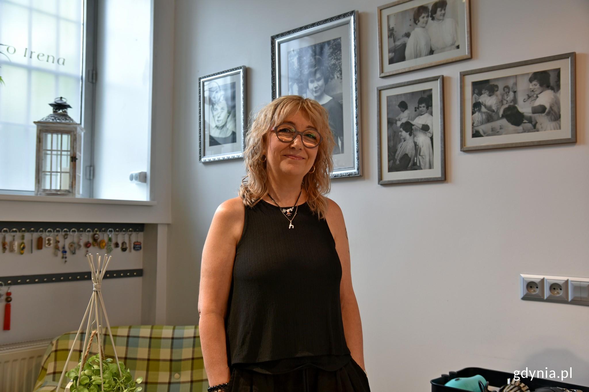 """Iwona Zagórska, właścicielka salonu fryzjerskiego """"Eco Irena"""". W tle zdjęcia Ireny - założycielki salonu // fot. Magdalena Czernek"""
