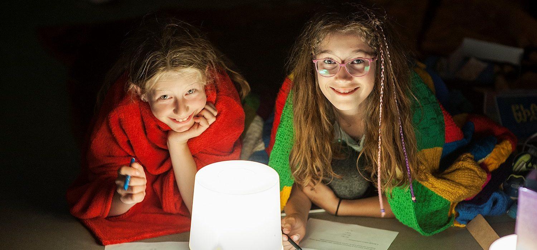 Dwójka dzieci pod kocami, trzymająca w rękach długopisy i kredki. Oświetla ich lampa.
