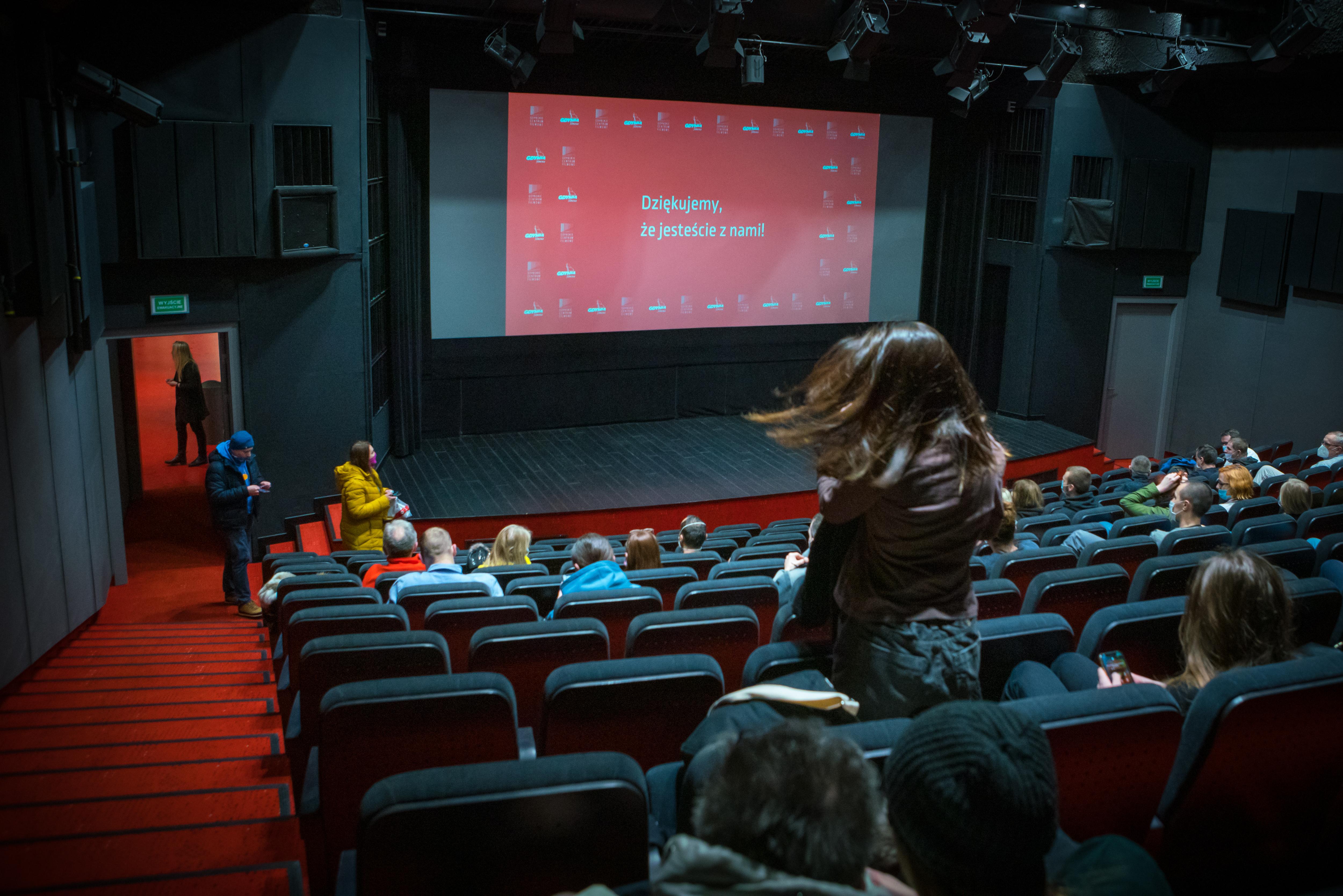 """Sala kinowa w Gdyńskim Centrum Filmowym, na ekranie wyświetla się biały napis na czerwonym tle """"Dziękujemy, że jesteście z nami!"""". Fot. Anna Rezulak / KFP"""
