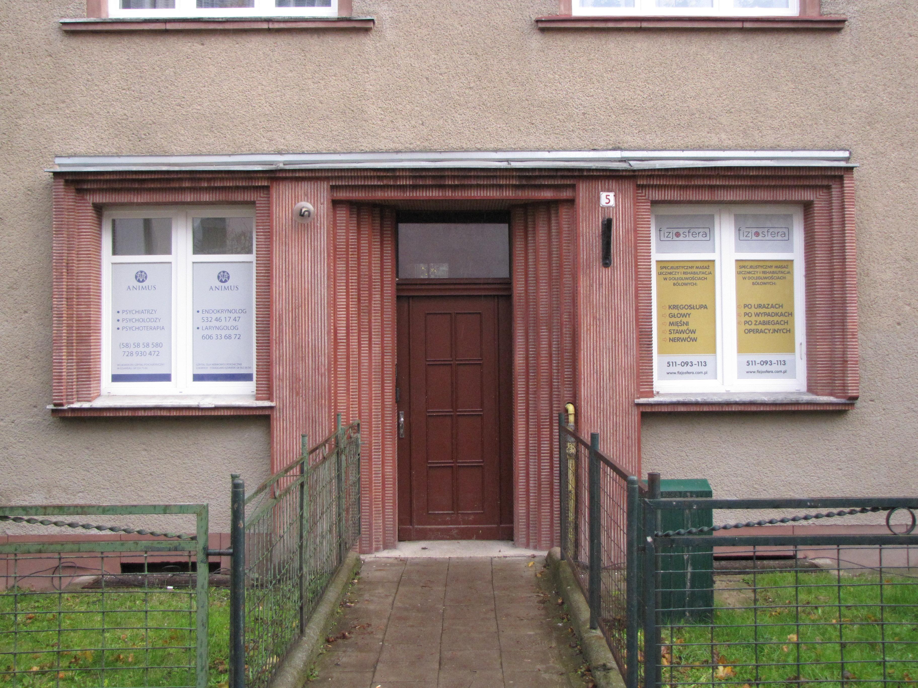 Portal kamienicy przy ul. Bema 5 z lat 30. XX w., w który włączono kompozycyjnie boczne okna, ozdobiony tynkiem szlachetnym w kolorze czerwonym.
