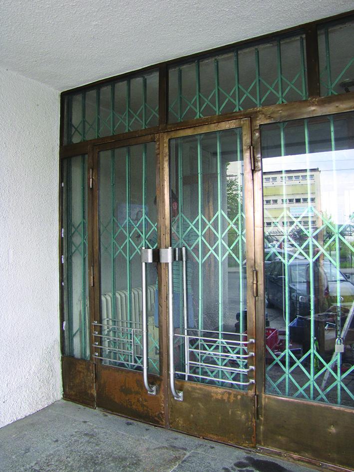 Drzwi bocznego wejścia do Sądu Rejonowego przy placu Konstytucji 5. Jedyny w Gdyni przykład metalowych drzwi z lat 30. XX w., w których konstrukcja w kolorze mosiądzu została zestawiona z pochwytami z kolorze srebrnym.
