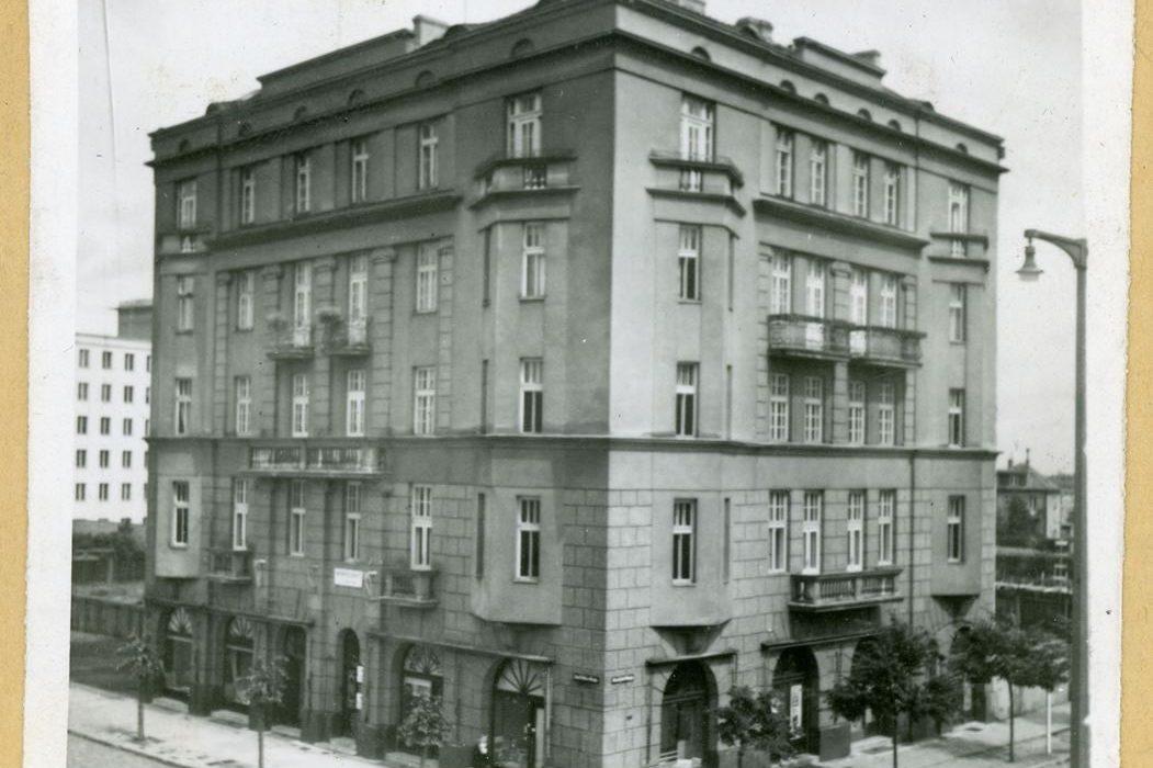 Zdjęcie archiwalne, czarnobiałe. Przedstawia kamienicę oraz fragmenty otaczającej ją ulicy i drzew.