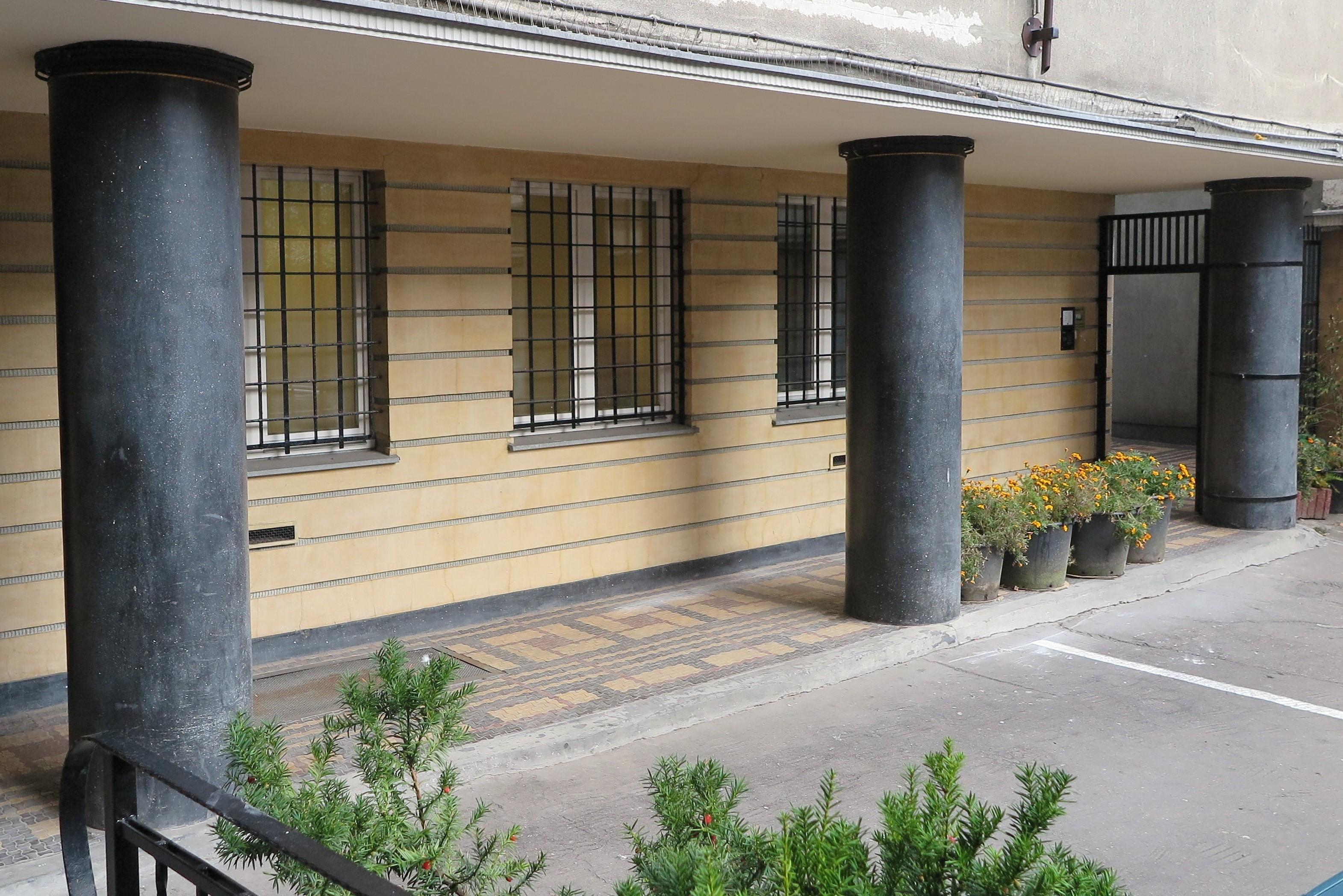 Wykończenie tynkarskie podcienia w budynku przy ul. 3 Maja 27-31 z tynkami szlifowanymi imitującymi kamień – żółtym na ścianie i czarnym na kolumnach. Jeden z najlepszych w Gdyni przykładów rzemiosła budowlanego z lat 30. XX w.