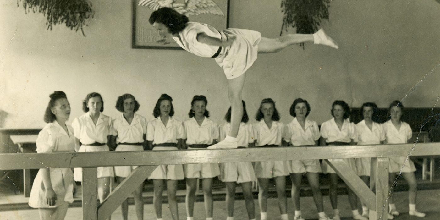Zdjęcie archiwalne wykonane w sepii. Grupa kobiet podczas ćwiczeń gimnastycznych. Jedna z nich wykonuje ćwiczenia na drewnianej platformie.