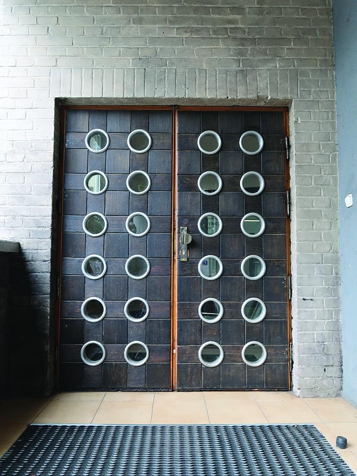 Drzwi głównego wejścia do siedziby Stowarzyszenia YMCA Gdynia przy ul. Żeromskiego 28, z okładziną z czarnego dębu i aluminiowymi oprawami okrągłych przeszkleń.