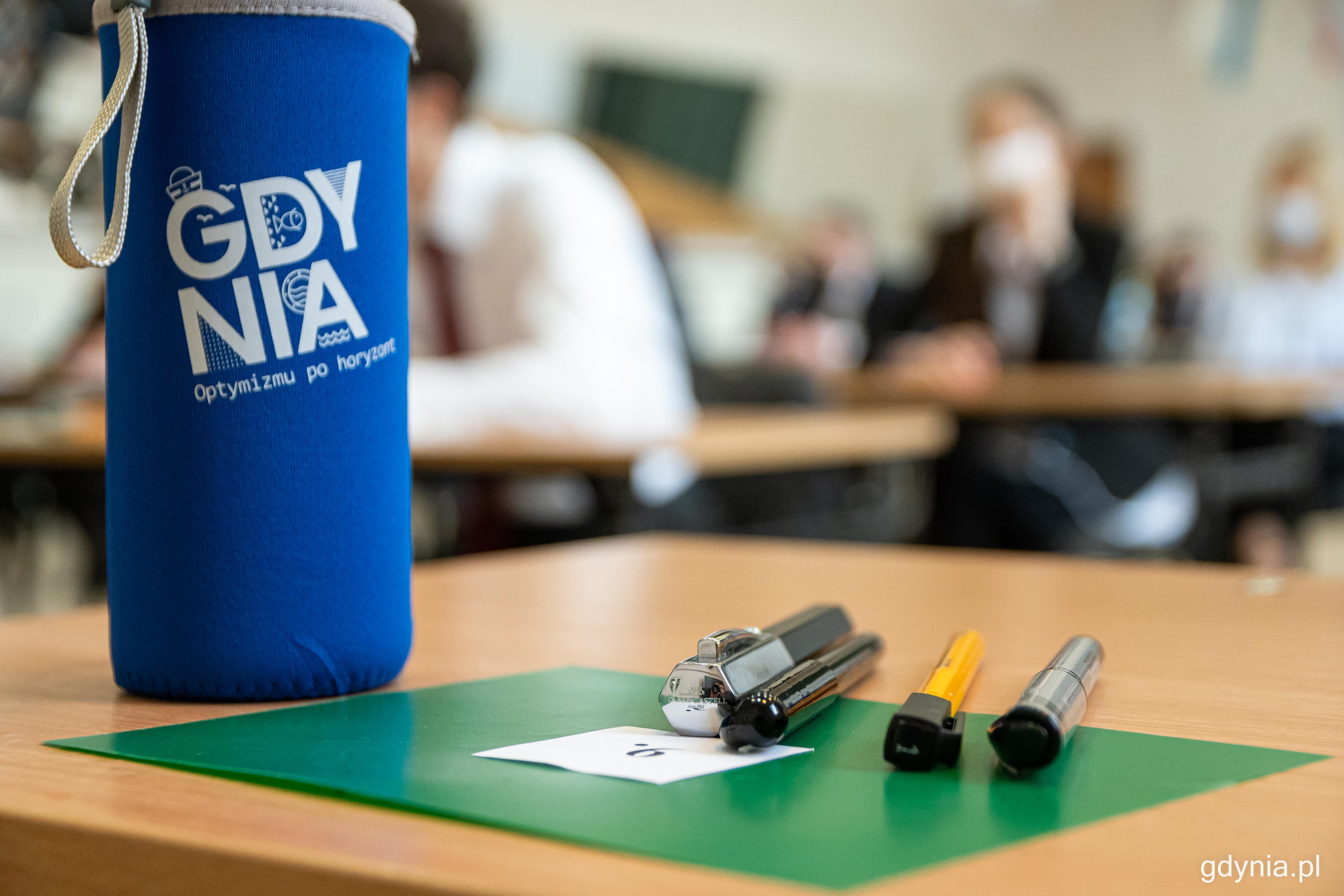 """Szklane butelki wielokrotnego użytku dla gdyńskich maturzystów. Na materiałowym etui widnieje hasło """"Optymizmu po horyzont"""". Fot. Kamil Złoch"""