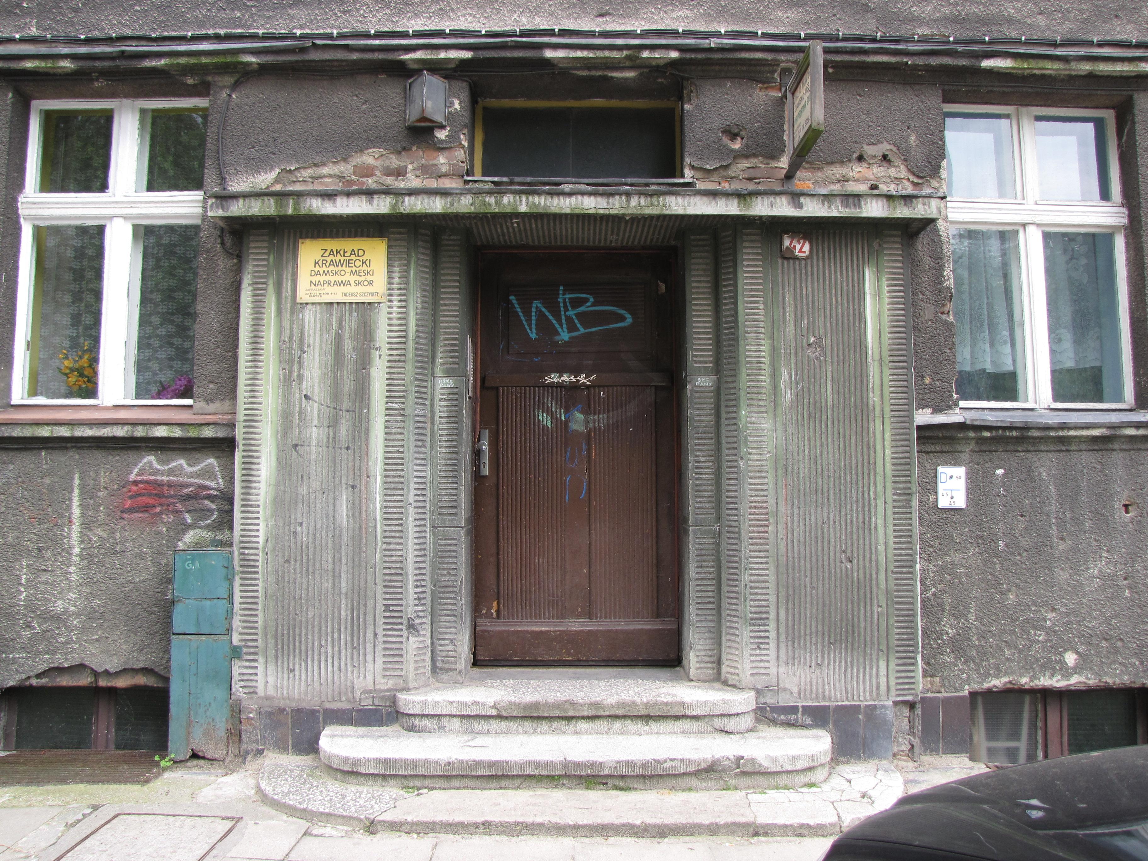 Portal kamienicy przy ul. Słowackiego z lat 30. XX w., dekorowany tynkiem szlachetnym z rowkami w kolorze zielonym.