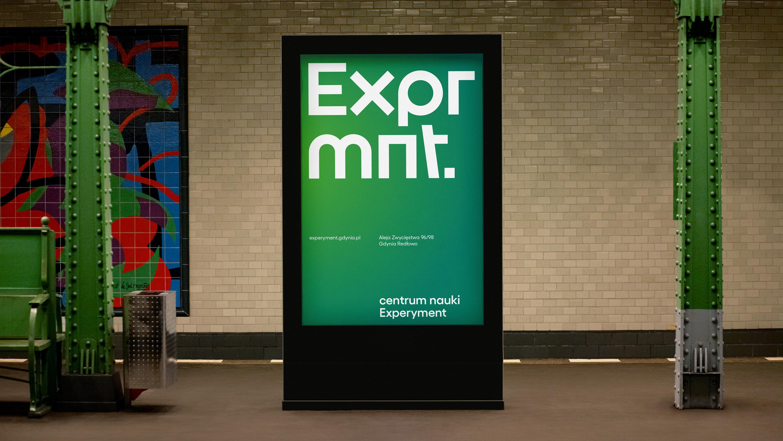 """Wizualizacja nowej identyfikacji Experymentu. Na zdjęciu reklama zewnętrzna (outdoorowa). Zielony plakat z dużym białym napisem """"Exprmnt."""" Poniżej, mniejszymi literami napisano: """"experyment.gdynia.pl Aleja Zwycięstwa 96/98 Gdynia Redłowo. Centrum Nauki Experyment"""". Projekt: TOFU Studio // fot. mat. prasowe"""