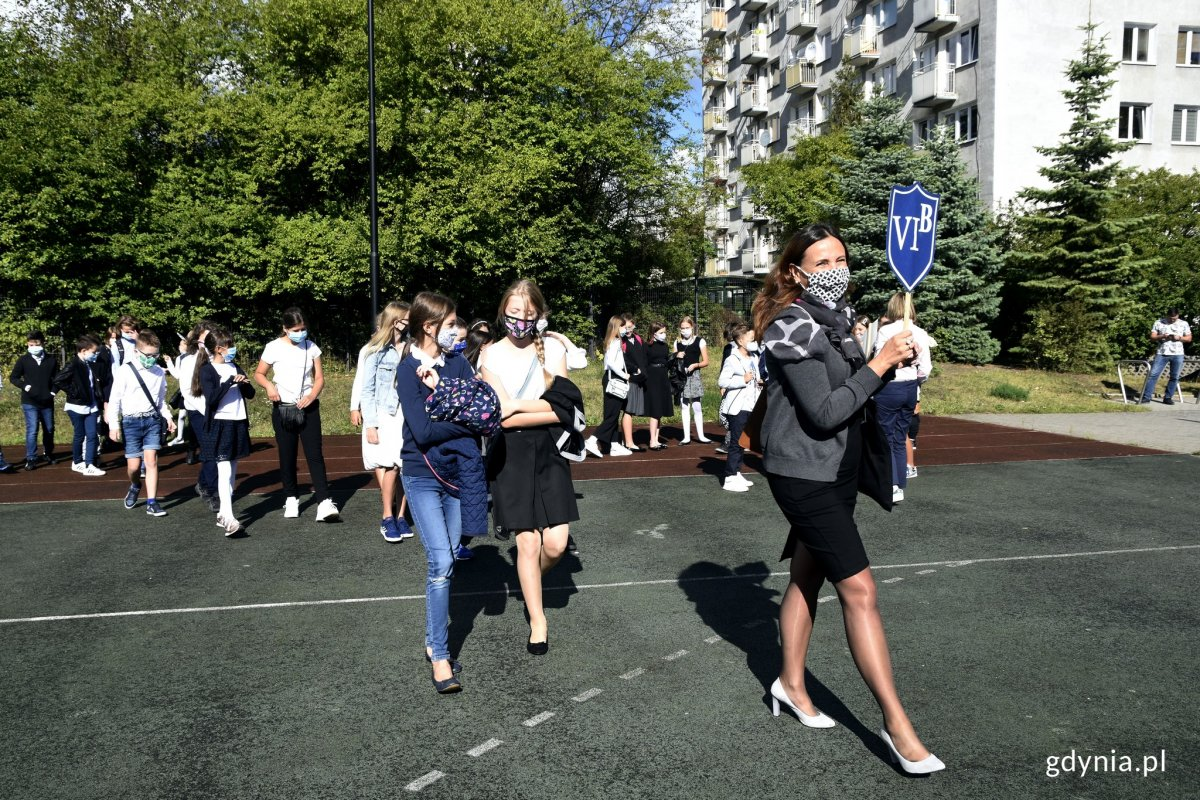 Rozpoczęcie roku w jednej z gdyńskich szkół. Nauczycielka trzyma w ręku niebieską tarczę z nazwą klasy. Za nią w dwuszeregu i odstępach idą uczniowie z maseczkami na twarzach // fot. Magdalena Czernek