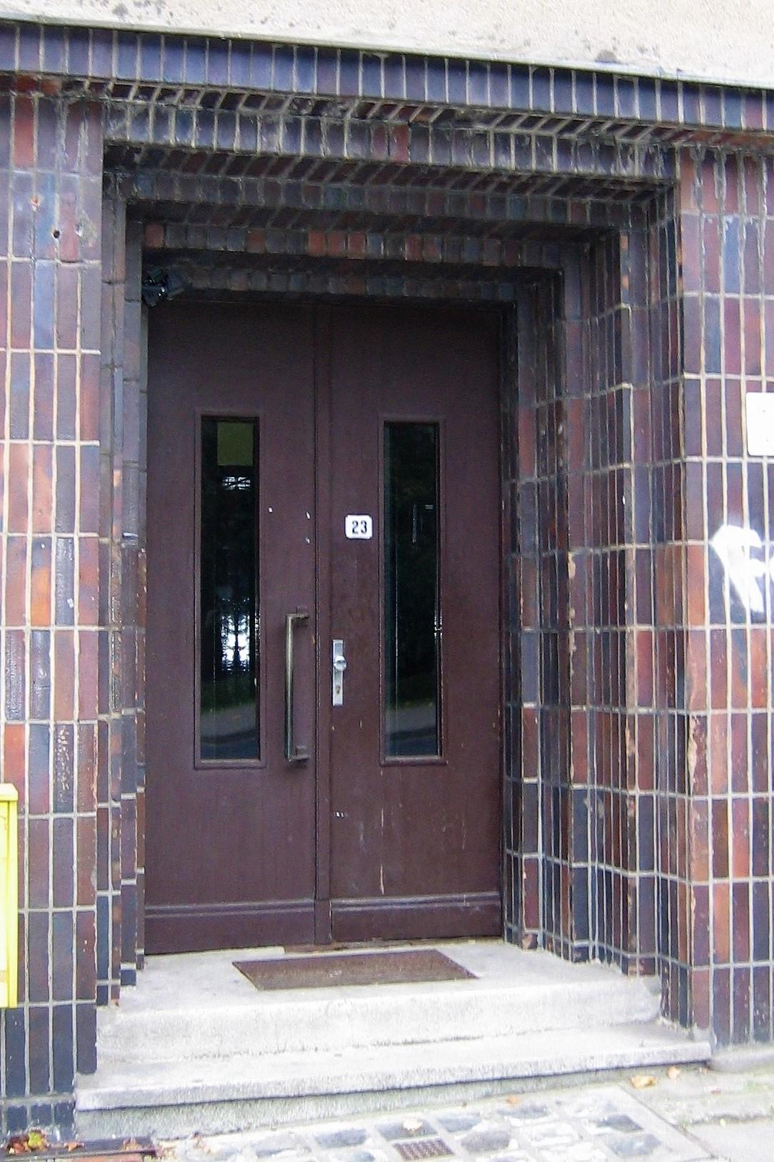 Portal części mieszkalnej budynku przy ul. Legionów, brązowymi płytkami oblicowano również elewacje pawilonu sklepowego.