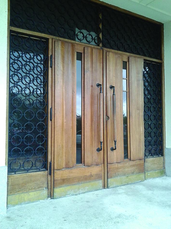 Wejście główne do budynku Wydziału Nawigacyjnego Uniwersytetu Morskiego przy al. Jana Pawła II 3, z drzwiami z motywem dekoracyjnej fali na powierzchni.