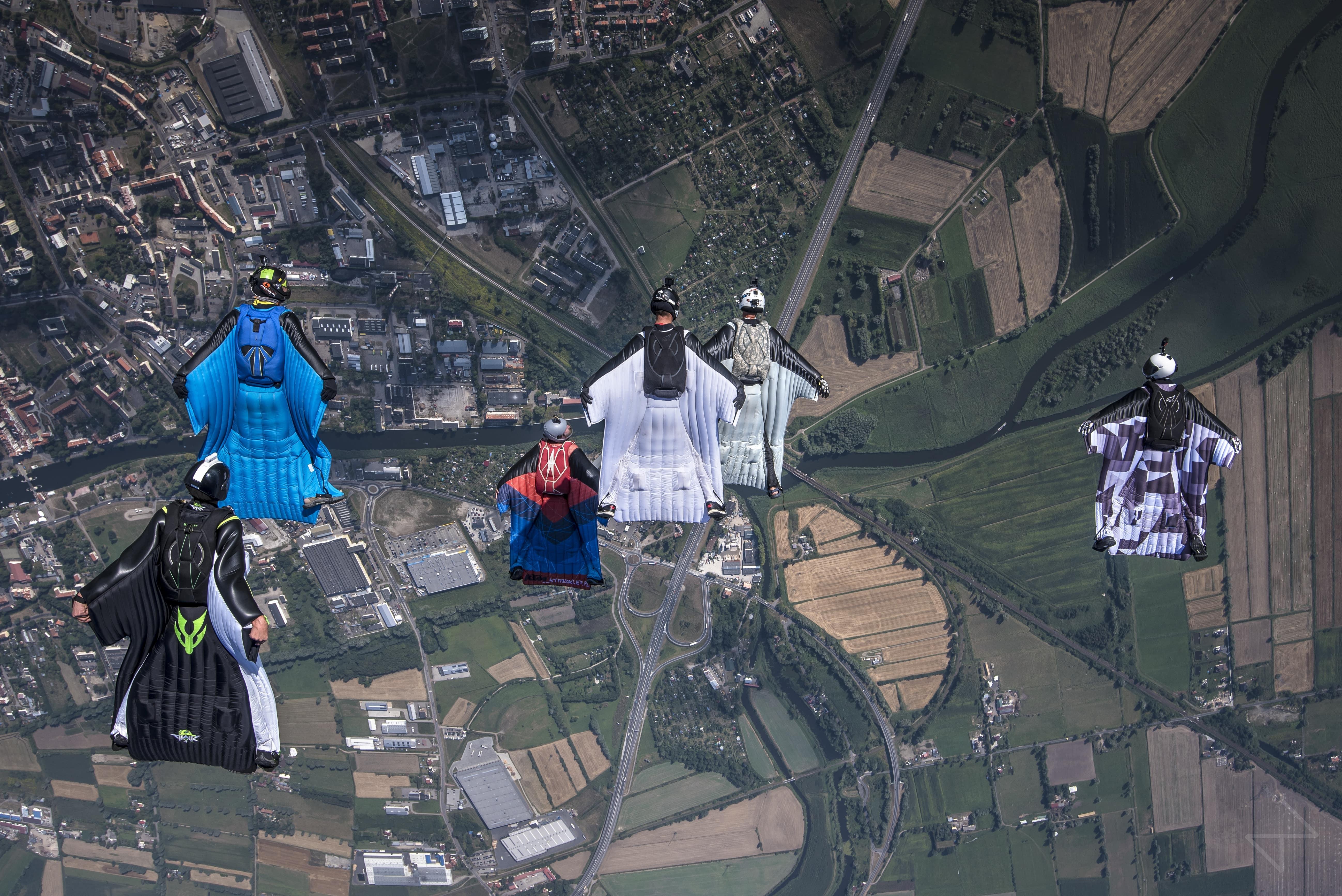 Skoczkowie w strojach wingsuit nad ziemią. // fot. mat. prasowe