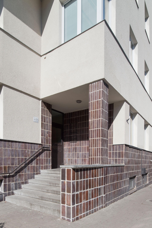 Strefa wejścia do budynku mieszkalnego ZUS przy ul. 3 Maja 22-24, brązowymi płytkami oblicowano ściany w podcieniu i cokół.