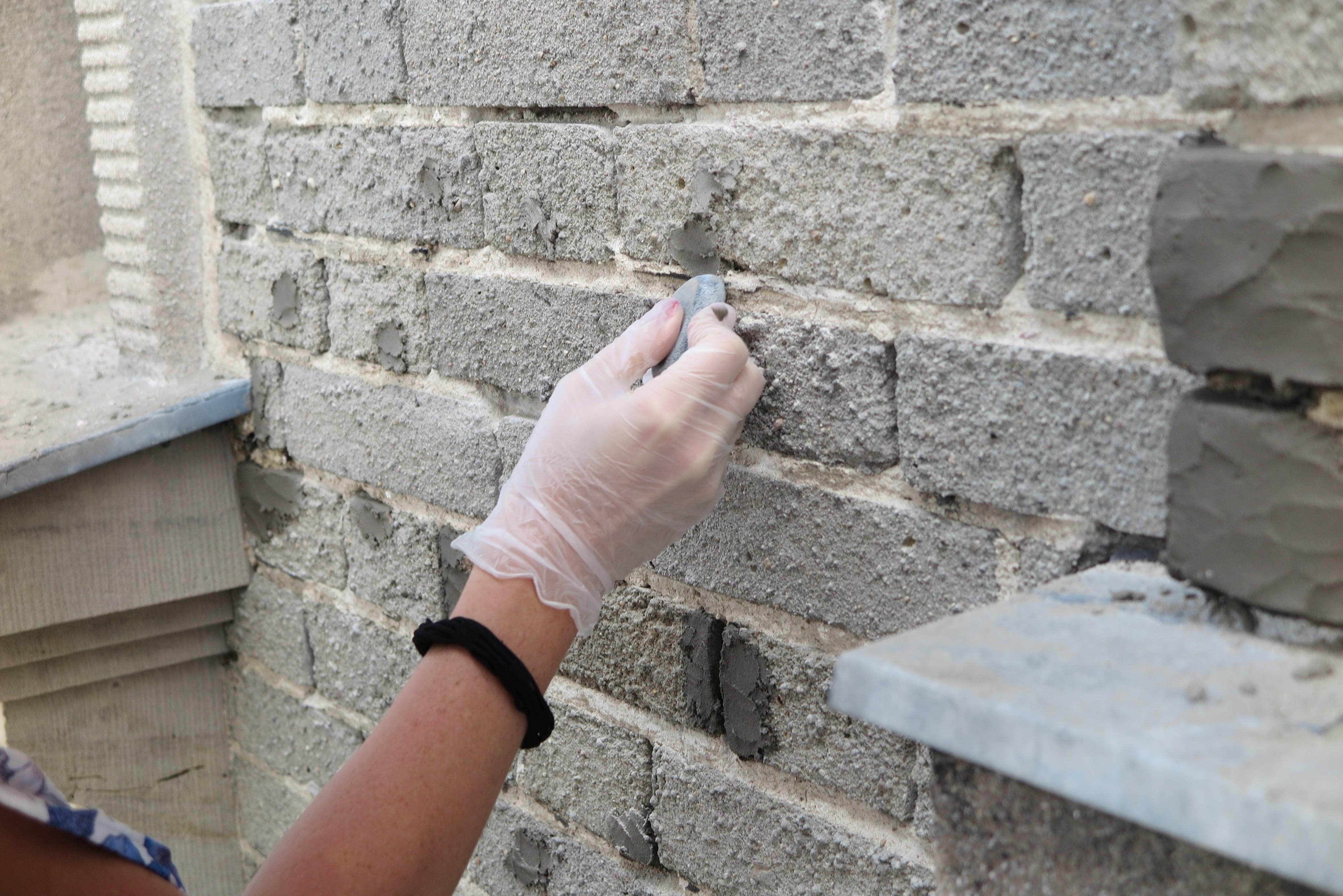 Przygotowanie masy cementowo-piaskowej i uzupełnianie ubytków cegieł na elewacji Uniwersytetu Morskiego.