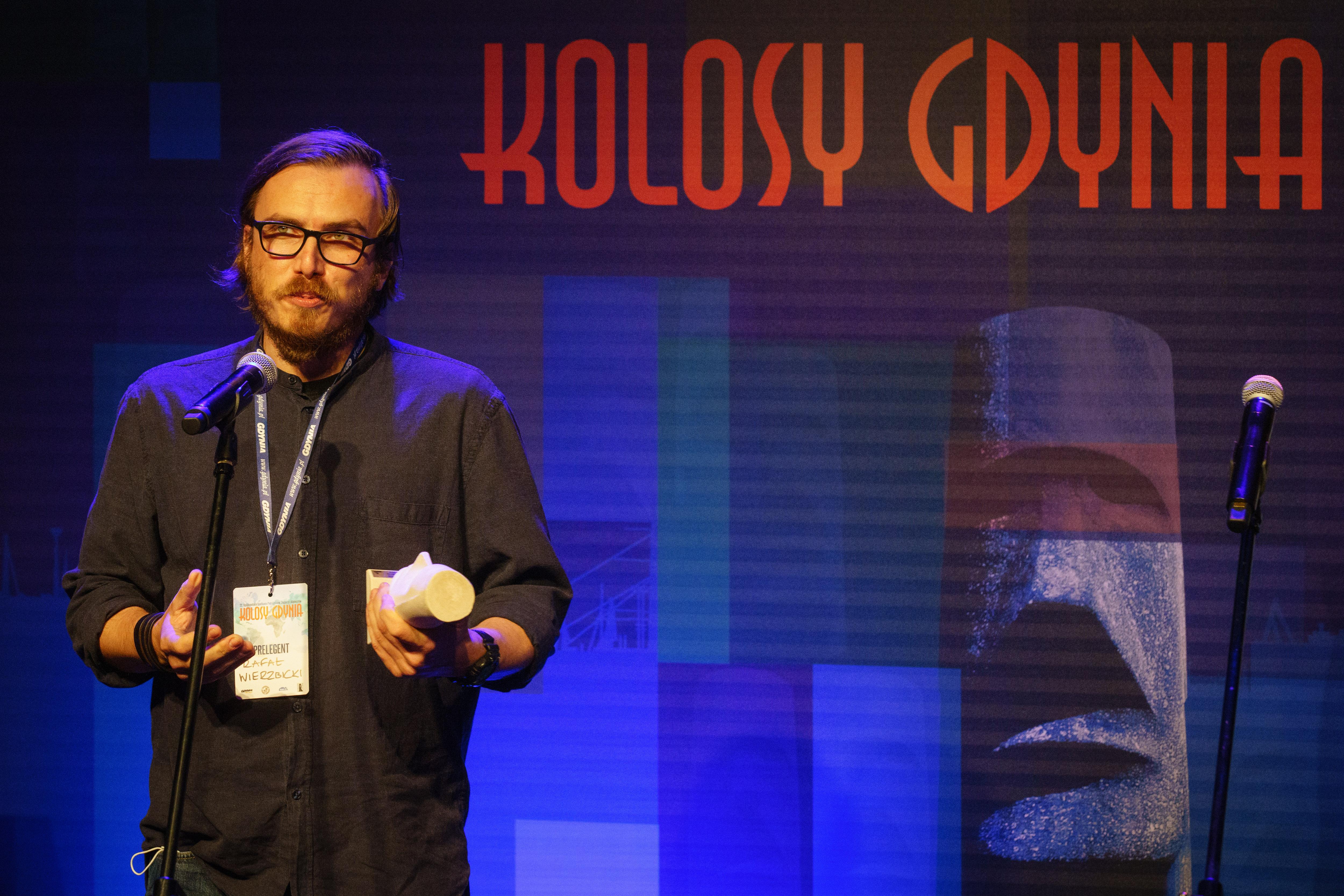 Rafał Wierzbicki ze statuetką w ręku mówi do mikrofonu // fot. Anna Rezulak