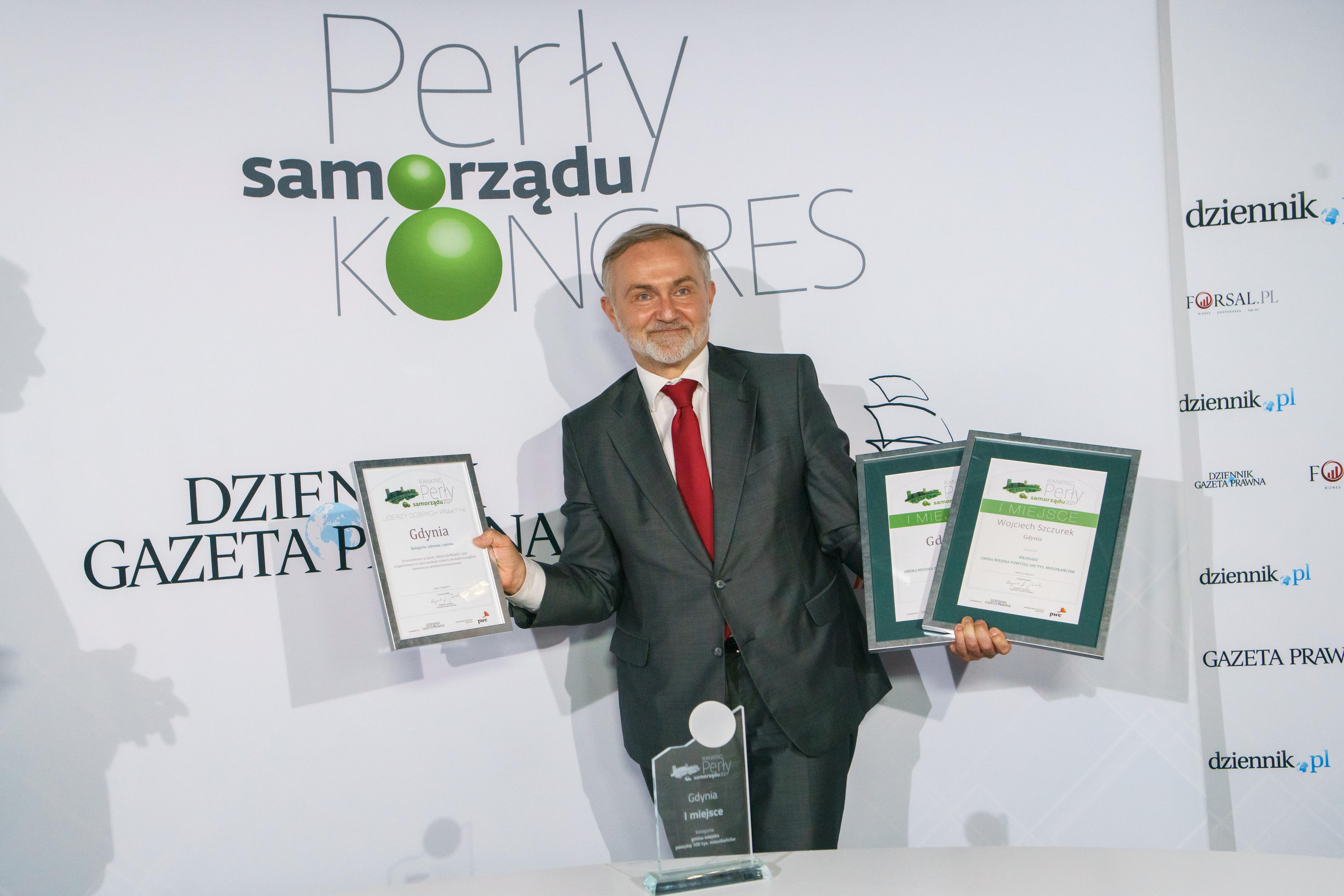 Krzysztof Jedlak i Wojciech Szczurek na tle białej ścianki. Wojciech Szczurek trzyma w rękach trzy dyplomy.