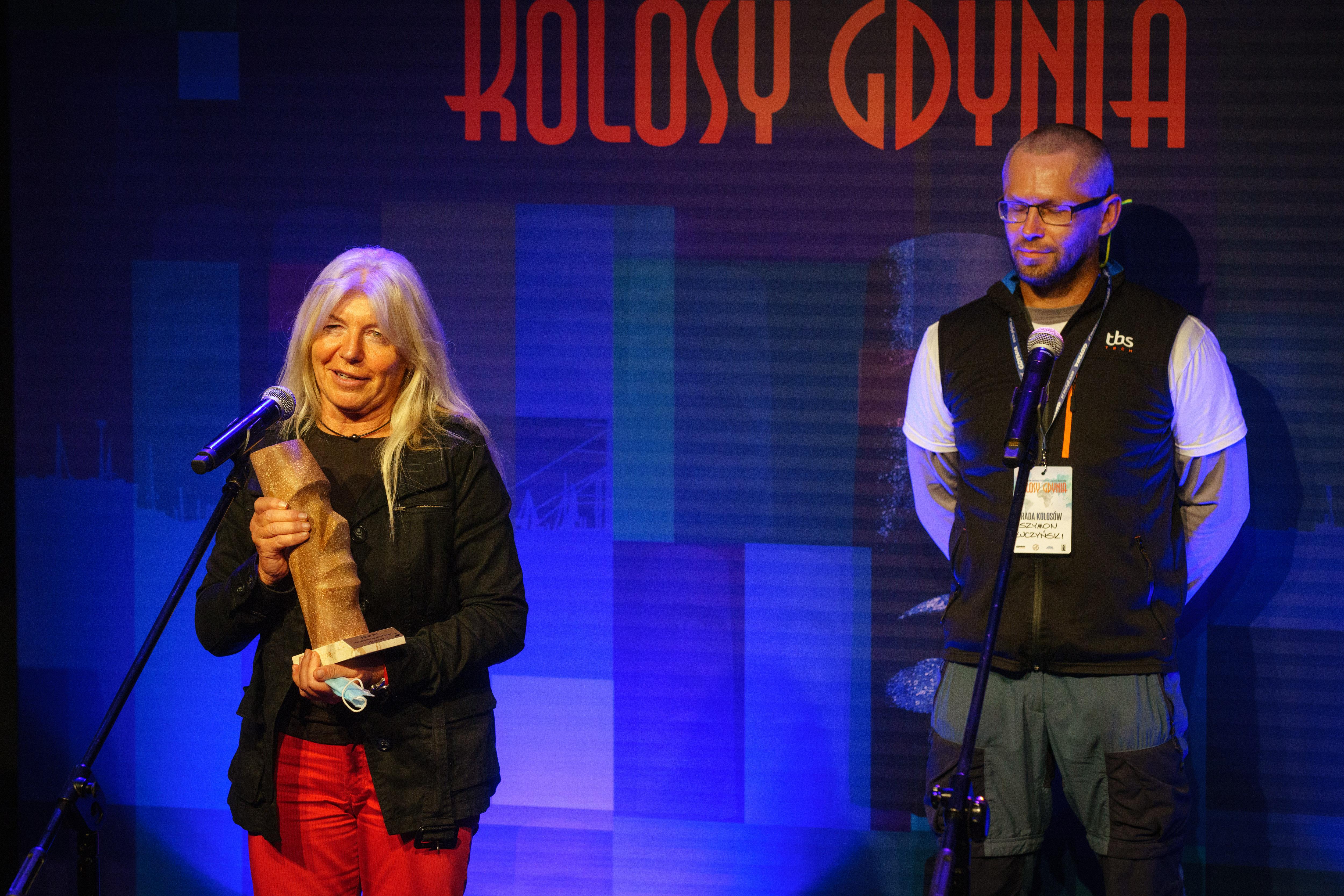 Joanna Pajkowska z Kolosem w ręku przemawia ze sceny. Z tyłu Szymon - Kuczyński - członek Rady Kolosów // fot. Anna Rezulak