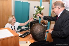 Dyrektor Urzędu Miasta Gdyni wręcza różę urzędnicze pracującej w sobotę w Sali Obsługi Mieszkańców w gdyńskim magistracie, fot. Michał Puszczewicz