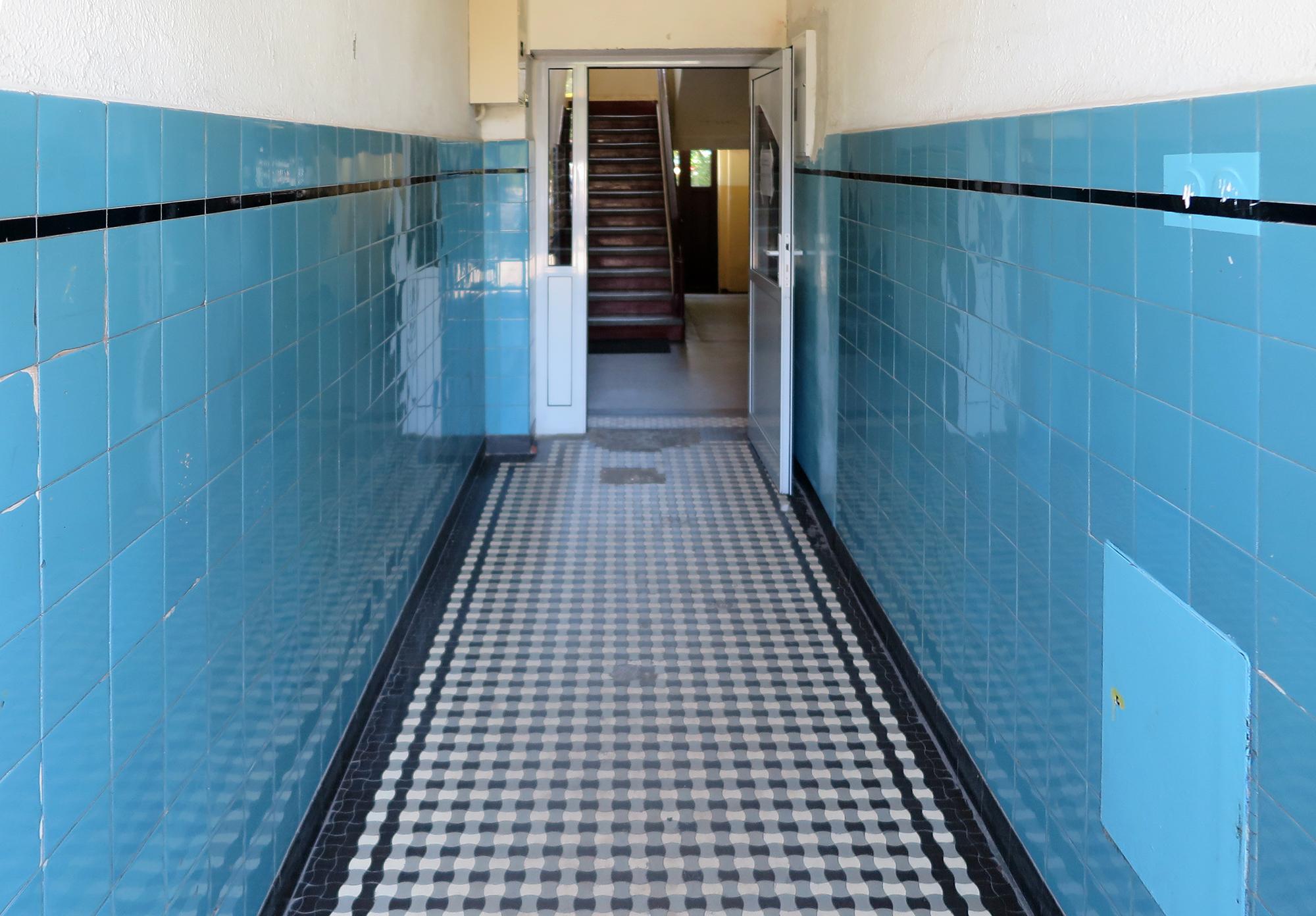 Strefa wejściowa w kamienicy przy ul. Portowej 3, dolne partie ścian wykończone ceramicznymi błękitnymi płytkami z wykończeniem z czarnym paskiem, posadzka zakomponowana z czarno-białych płytek tzw. gorsecików.