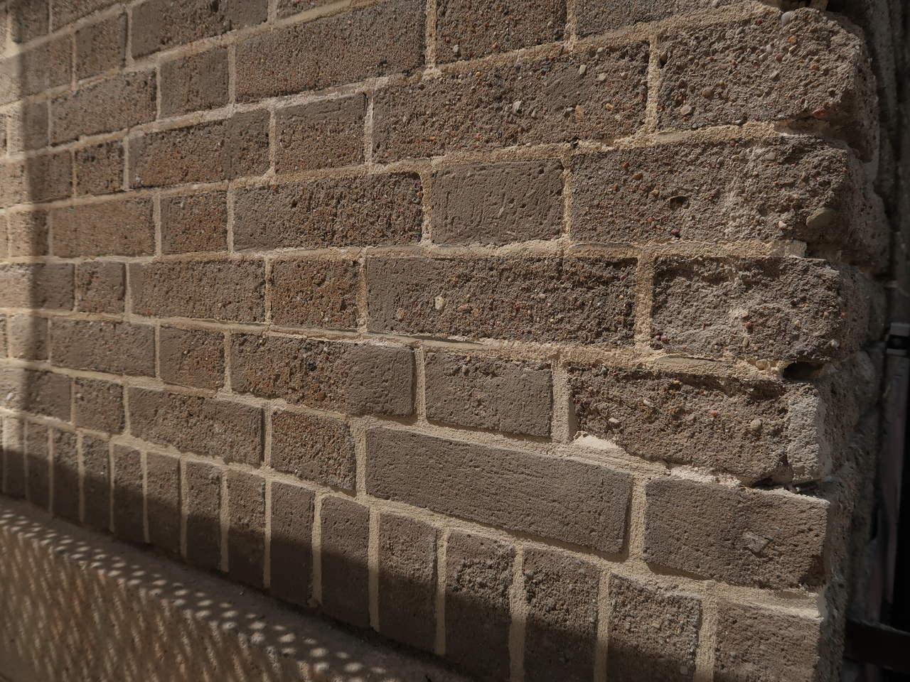 Fragment elewacji A budynku Uniwersytetu Morskiego po pracach konserwatorskich, widoczne uzupełnienia spoin oraz szarej cegły cementowej, narożnik przed remontem, fot. Biuro Miejskiego Konserwatora Zabytków
