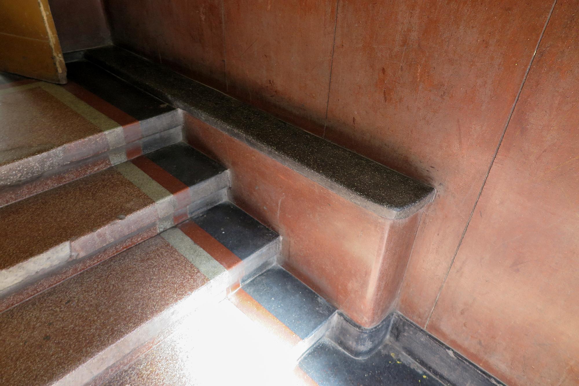 Fragment strefy wejściowej w kamienicy przy ul. Bema 15, dolne partie ścian oraz posadzka wykonana z lastryka o intensywnych kolorach.